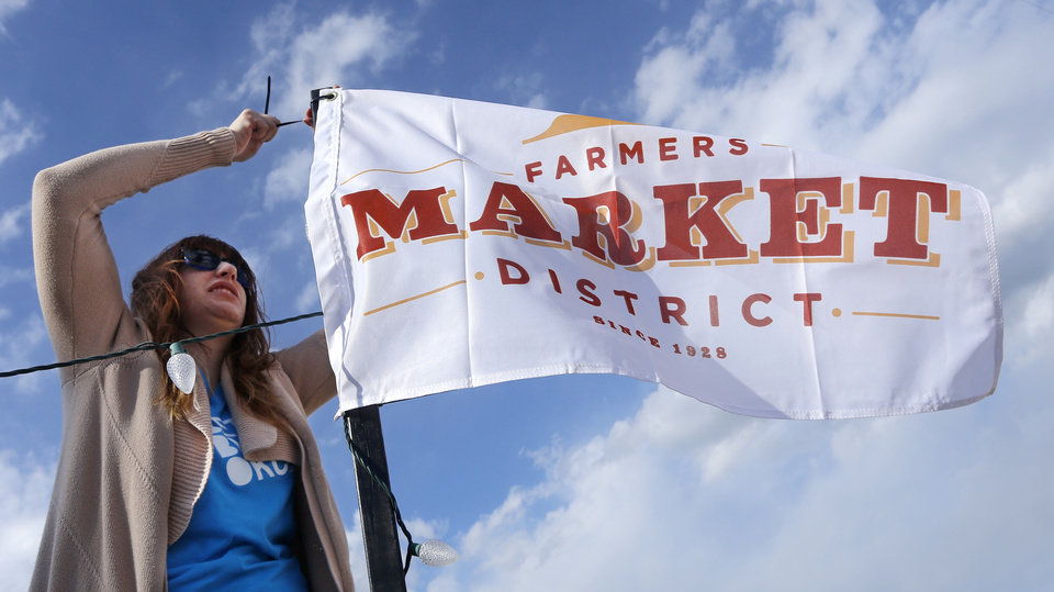 Photo - Ashley Terry ads flags to poles at the entrances while setting up for Saturday's Better Block Party in the Farmer's Market District. The flags include new branding created, pro bono, by Braid Creative.  DOUG HOKE - THE OKLAHOMAN