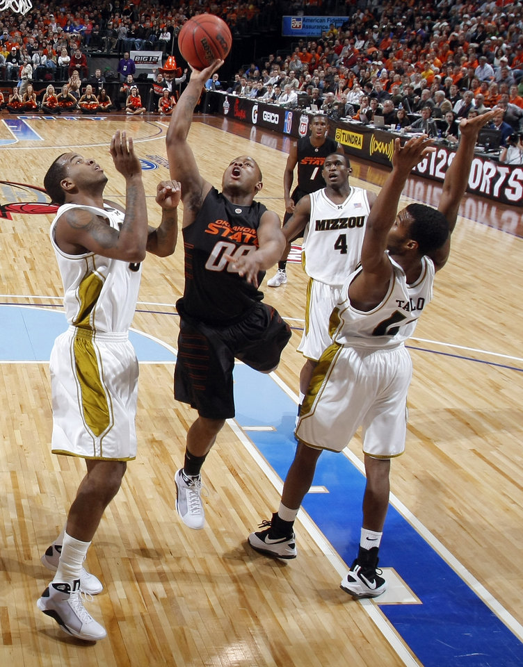 Photo - BIG 12 TOURNAMENT / COLLEGE BASKETBALL: OSU's Byron Eaton (00) puts up a shot between Missouri's Leo Lyons (5) and Zaire Taylor (11) in the semifinal game of the Big 12 Men's Basketball Championships between Oklahoma State University and The University of Missouri at the Ford Center on Friday, March 13, 2009, in Oklahoma City, Okla.  PHOTO BY CHRIS LANDSBERGER, THE OKLAHOMAN  ORG XMIT: KOD