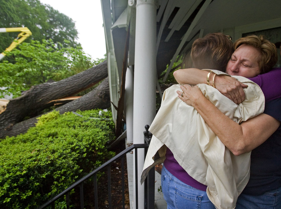 Photo - Mae Woody Christopher is comforted by a friend after a large oak tree split and crashed into her 7th Street home, Wednesday, April 27, 2011 in Tuscumbia, Ala. (AP Photo/TimesDaily,Daniel Giles)