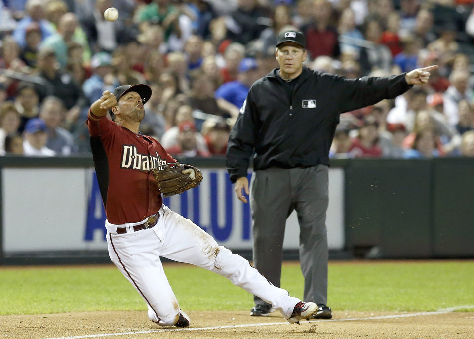 Photo - Arizona Diamondbacks' Martin Prado, left, throws the ball to first base on a ball hit by Chicago Cubs' Darwin Barney as umpire Paul Schrieber, right, signals a fair ball in the sixth inning of an exhibition baseball game, Friday, March 28, 2014, in Phoenix. (AP Photo/Ross D. Franklin)