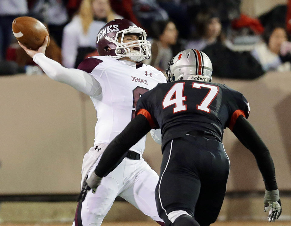 Photo - Jenks' quarterback Cooper Nunley unloads a pass under pressure from Union's Tristan Anderson during their 6A state championship game played at the University of Tulsa in Tulsa, OK, Dec. 12, 2013. MICHAEL WYKE/Tulsa World