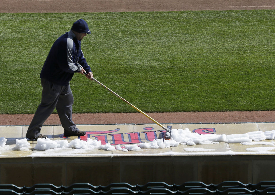 Photo - A Minnesota Twins grounds crew worker removes snow from the dugout roof prior to the start of the first game of a day/night baseball double header against the Miami Marlins Tuesday, April 23, 2013 in Minneapolis, Minn. Monday's game was postponed due to snow. (AP Photo/Jim Mone)