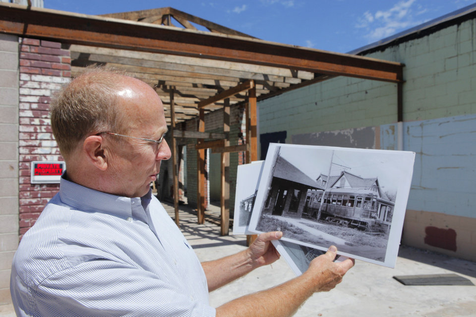 Barry Rice shows an old photo of the interurban depot at the site of the remains of the trolley station at 9 E First St. in downtown Edmond. Photo by David McDaniel, The Oklahoman