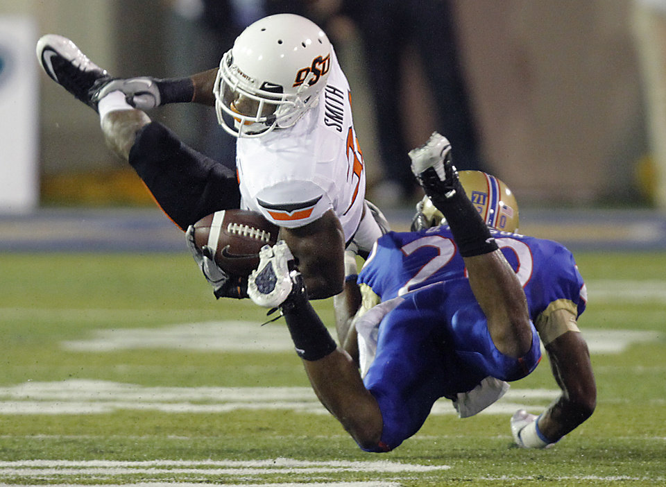 Photo - Oklahoma State's Jeremy Smith (31) is upended by Tulsa's Marco Nelson (20) during a college football game between the Oklahoma State University Cowboys and the University of Tulsa Golden Hurricane at H.A. Chapman Stadium in Tulsa, Okla., Sunday, Sept. 18, 2011. Photo by Chris Landsberger, The Oklahoman