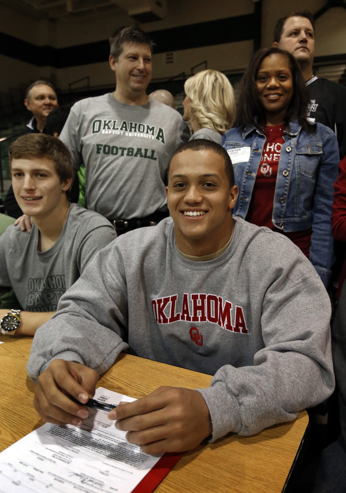 Photo - Jordan Evans, son of University of Oklahoma former defensive lineman Scott Evans, top right, signs a letter of intent to play for OU at a signing day assembly at Norman North High School on Wednesday, Feb. 6, 2013, in Norman, Okla.  Jordan's mother Tenika is behind him and at left is Oklahoma Baptist University comit Corbin Cleveland.  Behind Corbin is his father Rod Clevland.  Photo by Steve Sisney, The Oklahoman