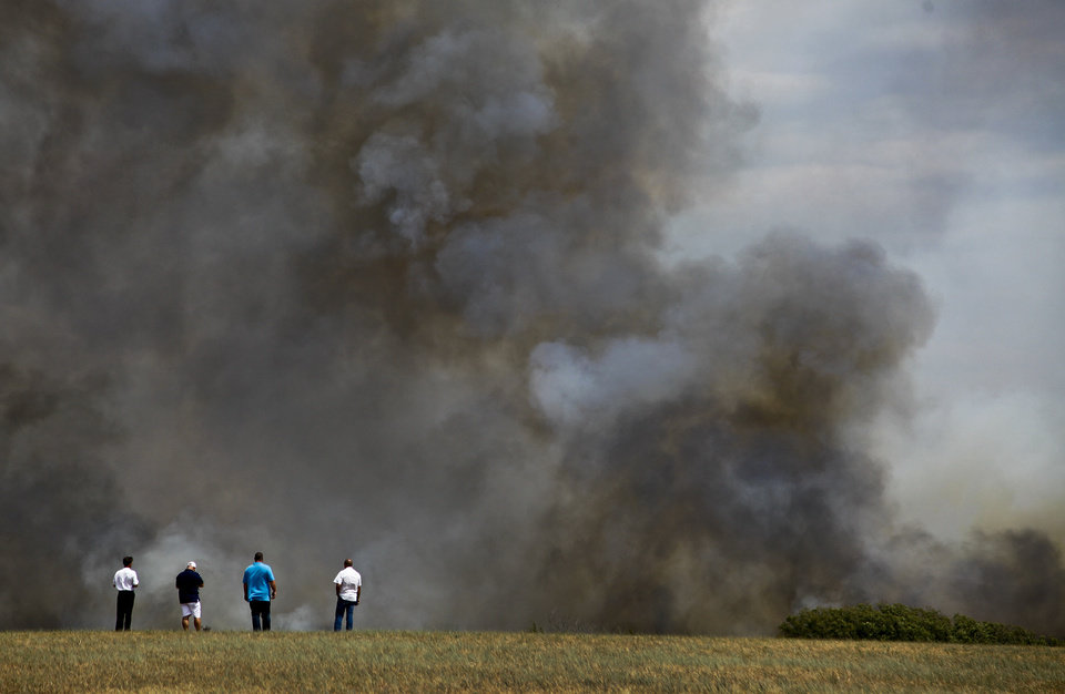 Photo - A concerned residents watche as the fire burns through a field near 63rd and Sooner Rd. on Tuesday, Aug. 30, 2011, in Oklahoma City, Okla. 