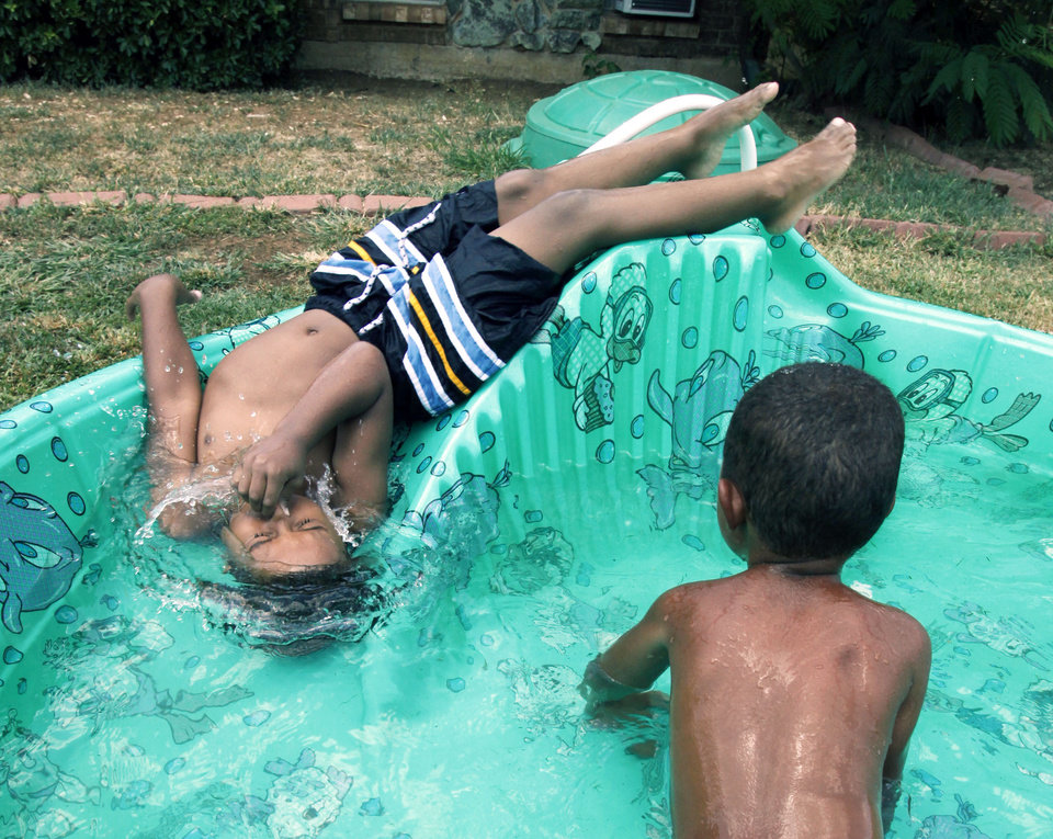 Five-year-old Dwight Williams Jr. (left) and three-year-old Prince Williams play in a pool in their front yard near NW 88th and Walker in Oklahoma City, OK, Thursday, July 21, 2011. By Paul Hellstern, The Oklahoman