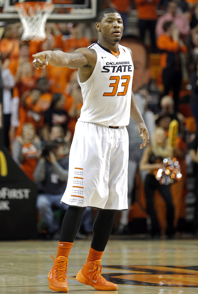 Photo - Oklahoma State's Marcus Smart (33) points to Phil Forte, III (13) after he scored a three-point basket during the men's college basketball game between Oklahoma State and Texas Tech at Gallagher-Iba Arena in Stillwater, Okla., Saturday, Feb. 22, 2014. OSU won 84-62. 
