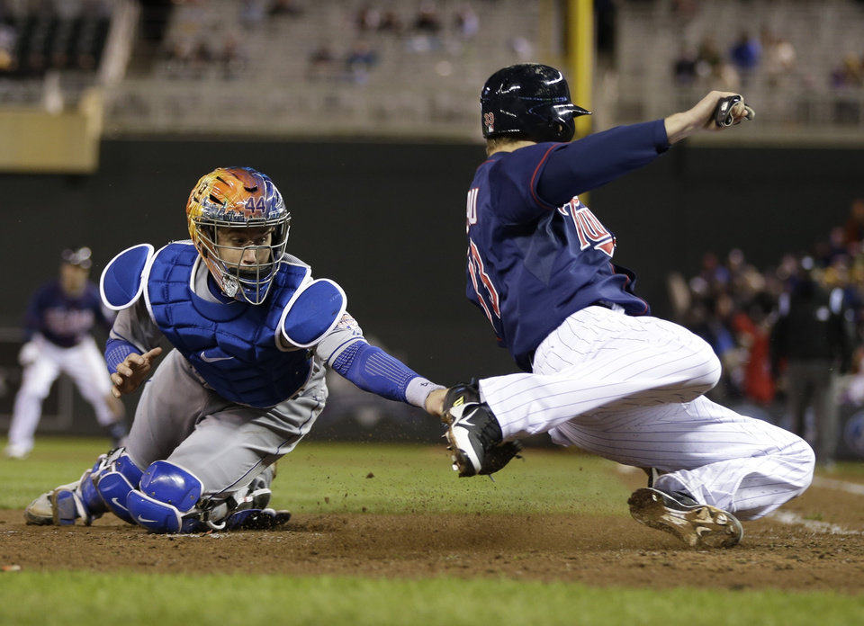 Photo - New York Mets' John Buck, left, attempts to tag Minnesota Twins' Justin Morneau, who scores on a two-run single by Ryan Doumit in the fifth inning of a baseball game, Friday, April 12, 2013, in Minneapolis. (AP Photo/Jim Mone)