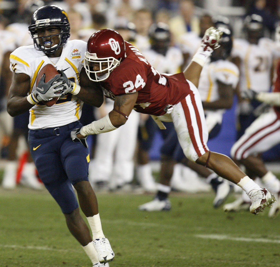 Photo - West Virginia's Tito Gonzales (83) pulls in a touchdown pass in front of Oklahoma's Marcus Walker (24) during the second half of the Fiesta Bowl college football game between the University of Oklahoma Sooners (OU) and the West Virginia University Mountaineers (WVU) at The University of Phoenix Stadium on Wednesday, Jan. 2, 2008, in Glendale, Ariz. 