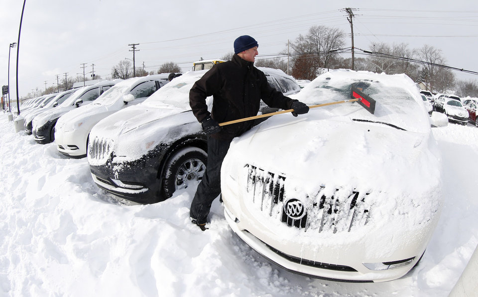 Photo - Matt Frame brushes off a Buick at Ray Laethem Buick-GMC in Detroit, Monday, Jan. 6, 2014. Michigan residents are preparing for diving temperatures as they dig out from more than 15 inches of snow in places. Snow wrapped up after starting during the weekend. Roads are slippery, with numerous crashes. In the southern Lower Peninsula, temperatures are to drop late Monday or early Tuesday as low as minus 15. (AP Photo/Paul Sancya)