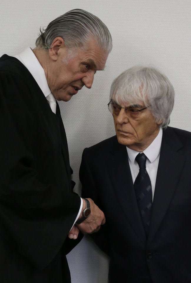 Photo - Formula One boss Bernie Ecclestone, right, talks to his lawyer Sven Thomas after he arrived for his trial in the regional court in Munich, southern Germany, Tuesday, Aug. 5, 2014. Ecclestone has been been on trial since April on charges of bribery and incitement to breach of trust. The charges involve a $44 million payment to banker Gerhard Gribkowsky, who's serving an 8 1/2-year sentence for taking the money. (AP Photo/Matthias Schrader)