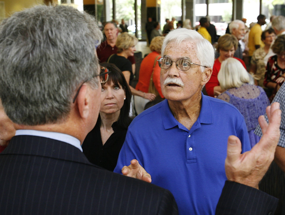 Photo - An unidentified man talks to Sen. Coburn after the formal town hall concluded. The lobby of Chase Bank in downtown Oklahoma City was crammed with more than 500 people who came to hear US Sen. Tom Coburn at a town hall meeting Monday afternoon, Aug. 24, 2009.  Photo by Jim Beckel, The Oklahoman