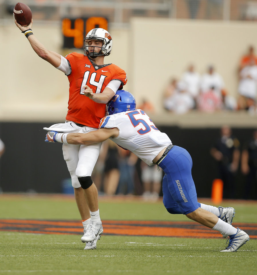 Photo - Oklahoma State's Taylor Cornelius (14) throws the ball as Boise State's Sam Whitney (53) hits him during a college football game between the Oklahoma State University Cowboys (OSU) and the Boise State Broncos at Boone Pickens Stadium in Stillwater, Okla., Saturday, Sept. 15, 2018. Oklahoma State won 44-21. Photo by Bryan Terry, The Oklahoman