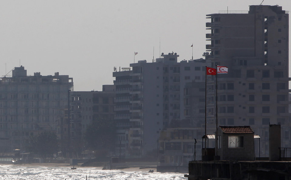 Photo - Turkish and Turkish Cypriot breakaway flags are seen on a military guard post in front of the deserted hotels in an area used by the Turkish military in the Turkish occupied area, in the abandoned coastal city of Varosha in Famagusta, southeast Cyprus, Friday, Jan. 17, 2014. The town's crumbling, war-scarred beachfront hotels have become an emblem of the country's division between Turks and Greeks. In 40 years, few have set foot inside the town, which remains heavily guarded by the Turkish army and twists of barbed wire. (AP Photo/Petros Karadjias, file)