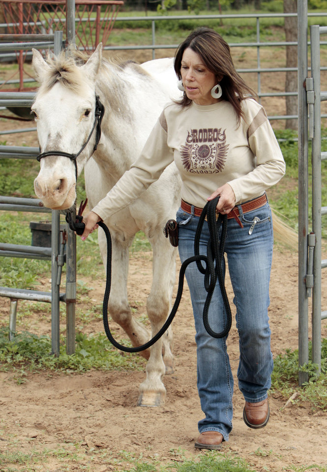 Photo - Lillian Guess, of Noble, leads her horse, Cherokee, out of a corral as she gets ready for last year's trail ride that commemorates Oklahoma's Land Run.  OKLAHOMAN ARCHIVES