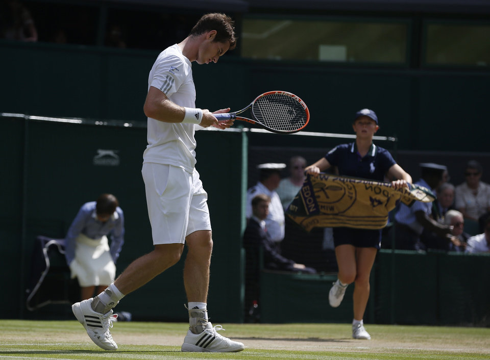 Photo - Andy Murray of Britain walks off court in a game break as a ball boy brings his towel during the men's singles quarterfinal match against Grigor Dimitrov of Bulgaria at the All England Lawn Tennis Championships in Wimbledon, London, Wednesday July 2, 2014. (AP Photo/Pavel Golovkin)