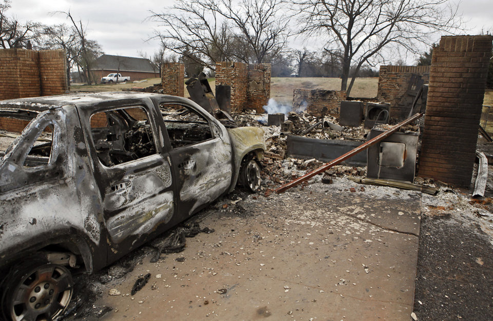 Photo - A burned out truck sits in the drive way of a house that was destroyed by wildfires near Reno Avenue and Hiawassee Road on Friday, April 10, 2009, in Midwest City, Okla.  Photo by Chris Landsberger, The Oklahoman