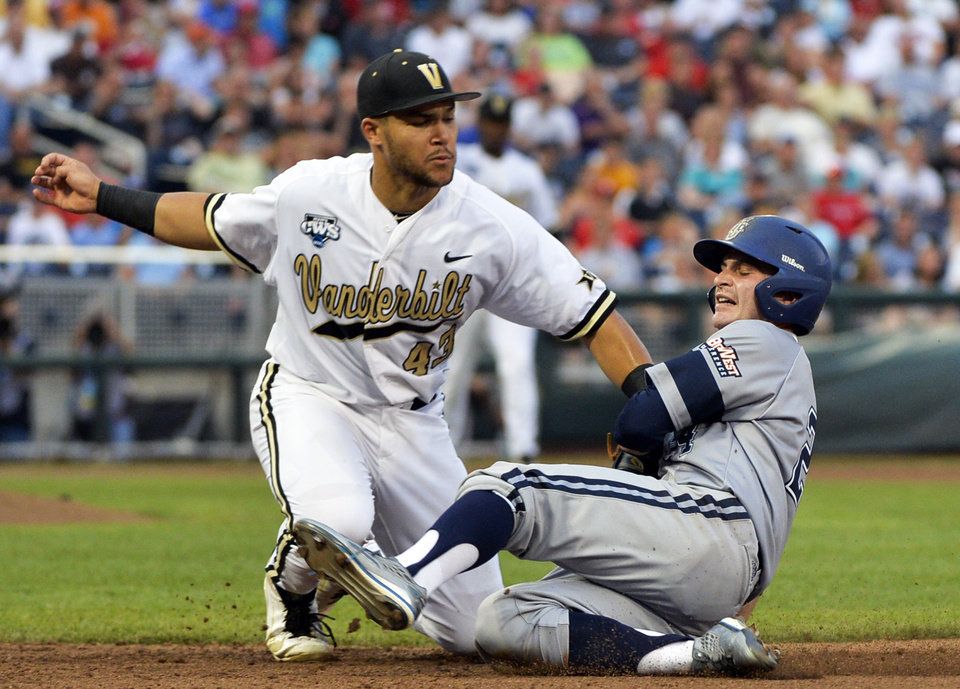 Photo - Vanderbilt first baseman Zander Wiel (43) tags out UC Irvine right fielder Kris Paulino, right, who was caught stealing in the fourth inning of an NCAA baseball College World Series game in Omaha, Neb., Monday, June 16, 2014. (AP Photo/Ted Kirk)