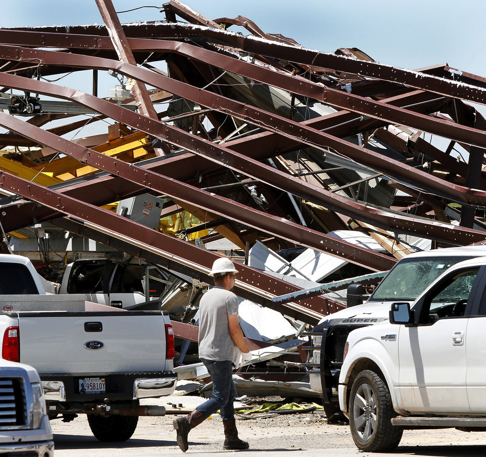 Photo - A worker who was part of a crew that worked Saturday afternoon, June 1, 2013, to remove equipment from this large storage building walks past mangled steel in  this heavily damaged supply yard for Cactus Drilling Company on State Highway 66 in El Reno on Saturday, June 1, 2013. Employee David Stottemyre was working in the lot when the tornado took aim at the plant. Stottemyre ran inside the large supply storage building and took shelter as the tornado passed over, leaving the building in a twisted pile of steel and metal. He was not injured.  Photo  by Jim Beckel, The Oklahoman.
