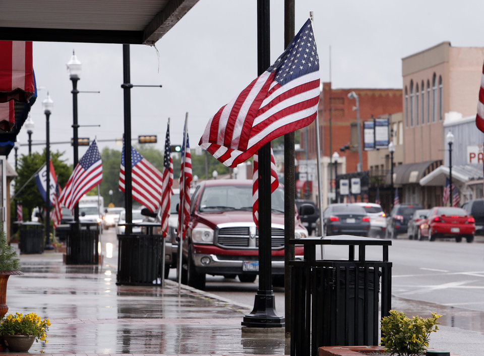 "Photo - Main Street in Davis is lined with flags on Friday in celebration of ""Love Your Flag Day.""  PHOTO BY STEVE SISNEY, THE OKLAHOMAN  STEVE SISNEY -"