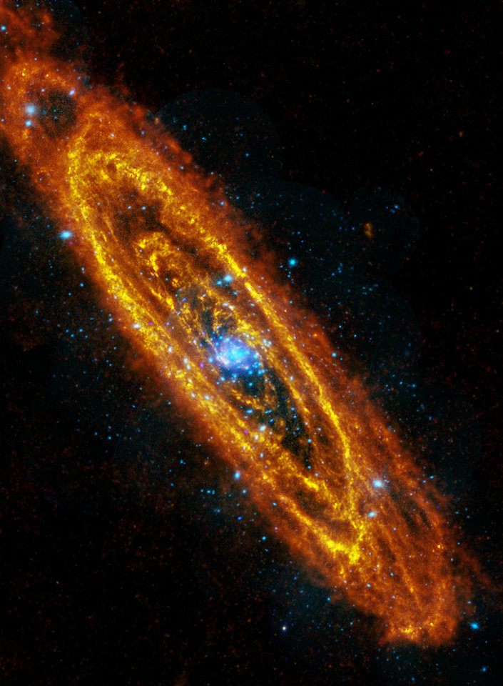 Photo - This image provided by NASA Wednesday Jan. 5, 2011 is the most detailed image of the Andromeda Galaxy ever taken at far-infrared wavelengths. The Herschel infrared space telescope captured the image during Christmas 2010. The image is a combination of observations from the Herschel Space Observatory taken in infrared light (seen in orange hues), and the XMM-Newton telescope captured in X-rays (seen in blues). Astronomers are  looking for thousands of Internet volunteers, to identify and count clusters of stars of the Andromeda galaxy. Astronomers from Utah to Europe say it would take them too long to study that many images and they need help.  (AP Photo/NASA, ESA)