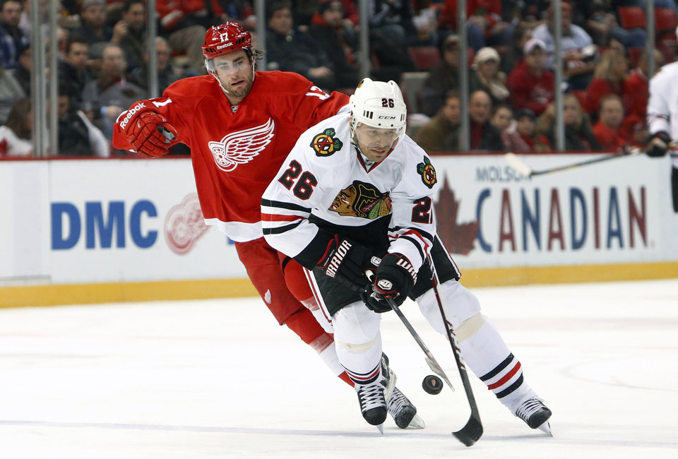 Photo - Chicago Blackhawks center Michal Handzus (26), of Czech Republic, tries to control the puck as Detroit Red Wings right wing Patrick Eaves defends in the first period of an NHL hockey game Wednesday, Jan. 22, 2014, in Detroit. (AP Photo/Paul Sancya)