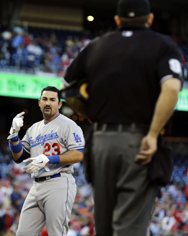 Photo -   Los Angeles Dodgers' Adrian Gonzalez talks with umpire Brian Knight after he struck out during the seventh inning of the first baseball game of a doubleheader against the Washington Nationals at Nationals Park, Wednesday, Sept. 19, 2012, in Washington. The Nationals won the first game 3-1. (AP Photo/Alex Brandon)