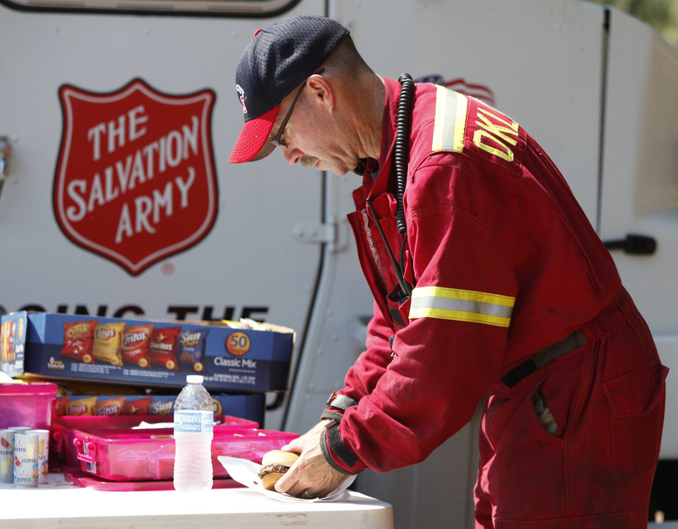 Photo - Oklahoma City Fire Department Lt. Brandon Lewis prepares his hamburger provided by the Salvation Army at the command center located at NE 63 and Sooner road in Oklahoma City , Wednesday, August 31, 2011. Photo by Steve Gooch, The Oklahoman
