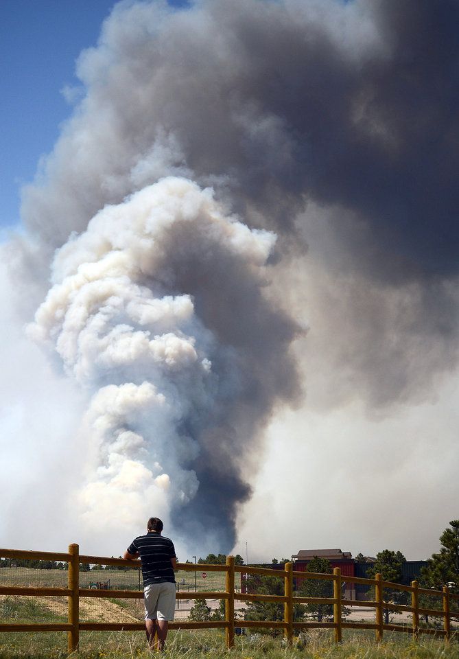 Photo - The Black Forest Fire burns out of control for a second straight day near Colorado Springs, Colo. on Wednesday, June 12, 2013. An evacuated resident watches a plume rise near his home. The fire has consumed at least 7500-8000 acres. It has destroyed 92 homes and damaged others. The erratic fire has forced the evacuation of thousands of people in the Black Forest and portions of Colorado Springs. (AP Photo/Bryan Oller)