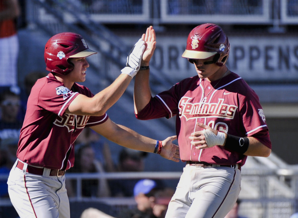 Photo -   Florida State's Jayce Boyd, right, is greeted by teammate Josh Delph after Boyd scored against Arizona on a double hit by Justin Gonzalez in the fourth inning of an NCAA College World Series baseball game in Omaha, Neb, Thursday, June 21, 2012. (AP Photo/Ted Kirk)