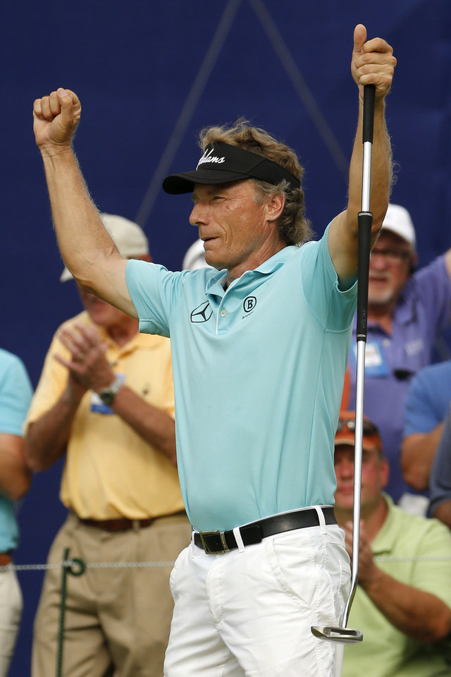 Photo - Bernhard Langer of Munich, Germany celebrates after sinking a birdie putt on the 18th green on the second hole of a sudden death playoff with Jeff Sluman to win the Senior Players Championship golf tournament at Fox Chapel Golf Club in Pittsburgh, Sunday, June 29, 2014. (AP Photo/Gene J. Puskar)