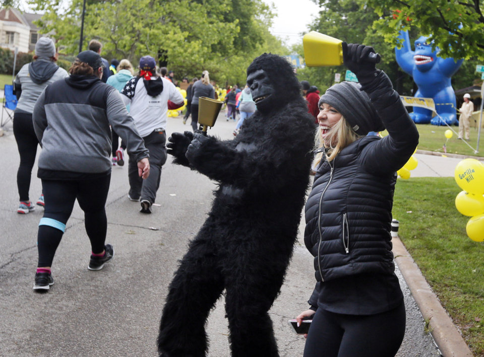 Photo - Erika Oliveira, right, and Ben Barenberg, in the gorilla costume, cheer on participants in the Oklahoma City Memorial Marathon along Gorilla Hill near NW 40 and Shartel Ave. in Oklahoma City, Sunday, April 30, 2017. Photo by Nate Billings, The Oklahoman