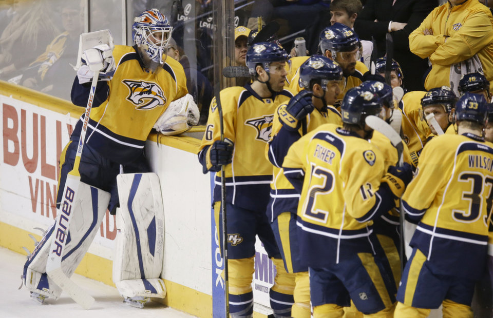 Photo - Nashville Predators goalie Devan Dubnyk, left, takes a break during a timeout in the first period of an NHL hockey game against the Colorado Avalanche, Saturday, Jan. 18, 2014, in Nashville, Tenn. The game is Dubnyk's first in goal for the Predators since being acquired from the Edmonton Oilers. (AP Photo/Mark Humphrey)