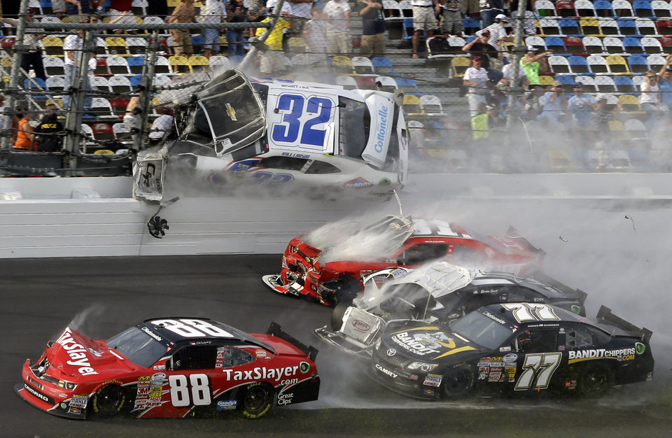 Photo - Kyle Larson (32) goes airborne into the catch fence in a multi-car crash including Dale Earnhardt Jr. (88), Parker Kligerman (77), Justin Allgaier (31) and Brian Scott (2) during the final lap of  the NASCAR Nationwide Series auto race at Daytona International Speedway, Saturday, Feb. 23, 2013, in Daytona Beach, Fla. (AP Photo/John Raoux)