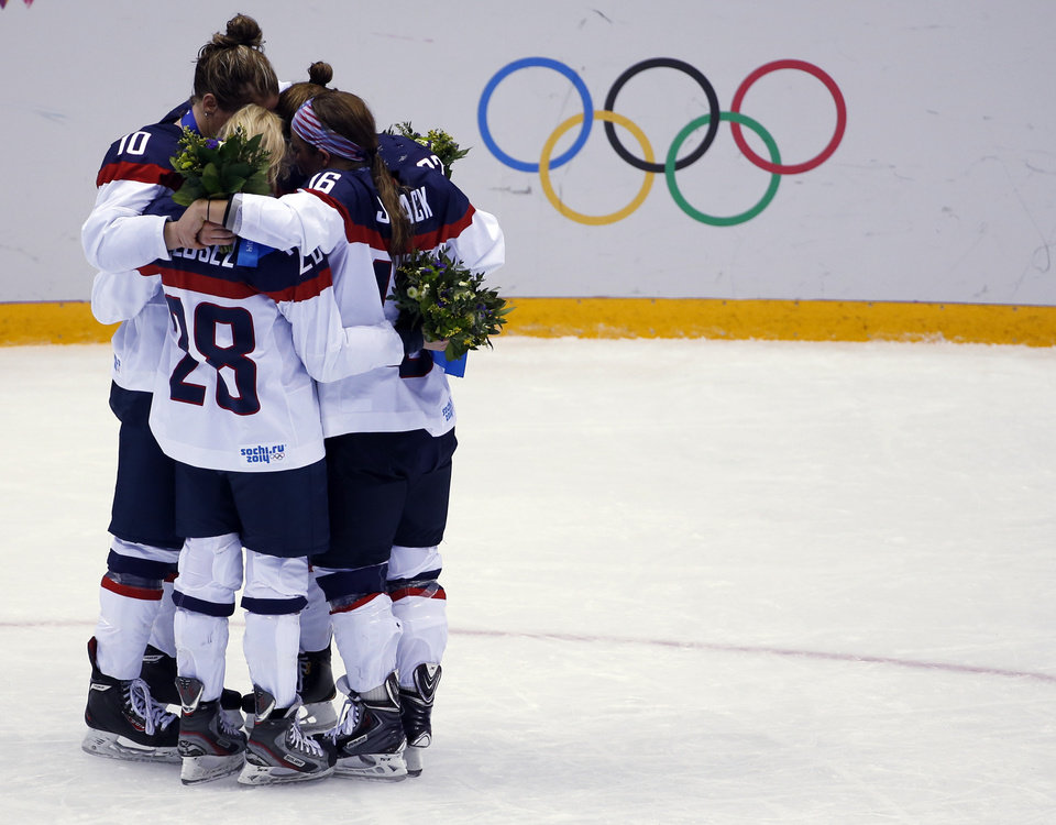 Photo - Meghan Duggan of the United States (10), Amanda Kessel of the United States (28) and Kelli Stack of the United States (16) hug after the medal ceremony for the women's ice hockey tournmant at the 2014 Winter Olympics, Friday, Feb. 21, 2014, in Sochi, Russia. Team USA won silver after losing to Canada 3-2 in overtime. (AP Photo/Petr David Josek)