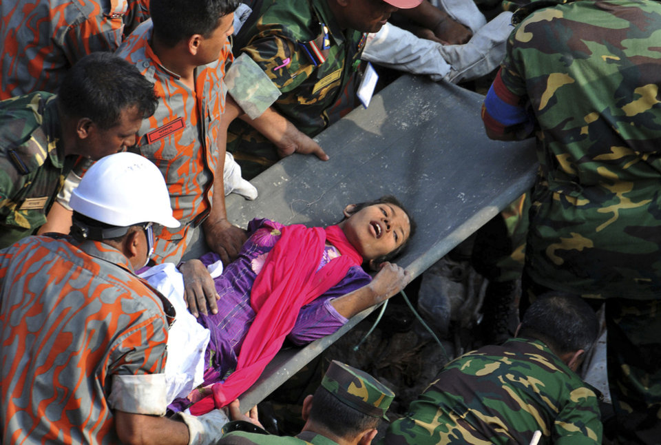 Photo - Rescuers carry a survivor pulled out from the rubble of a building that collapsed in Savar, near Dhaka, Bangladesh, Friday, May 10, 2013. Rescue workers in Bangladesh freed the woman buried for 17 days inside the wreckage of a garment factory building that collapsed, killing more than 1,000 people. Soldiers at the site said her name was Reshma and described her as being in remarkably good shape despite her ordeal. (AP Photo)