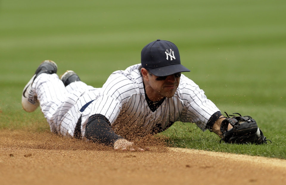 Photo - New York Yankees second baseman Brian Roberts makes a diving stop on a ground ball hit by Cincinnati Reds' Billy Hamilton during the fifth inning of a baseball game, Saturday, July 19, 2014, at Yankee Stadium in New York. Hamilton was out at first on the play. (AP Photo/Julio Cortez)