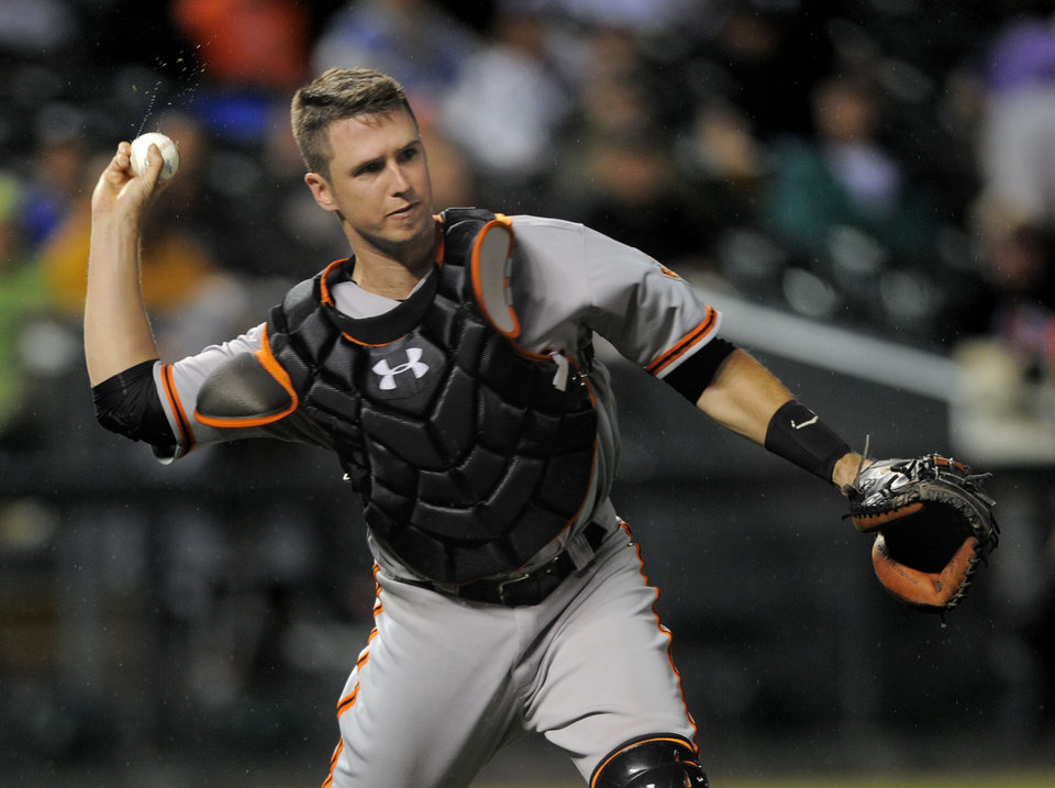 Photo -   San Francisco Giants catcher Buster Posey is late with a wet ball throw to first allowing Colorado Rockies' Dexter Fowler a single during the third inning of a baseball game Tuesday, Sept. 11, 2012, in Denver. (AP Photo/Jack Dempsey)