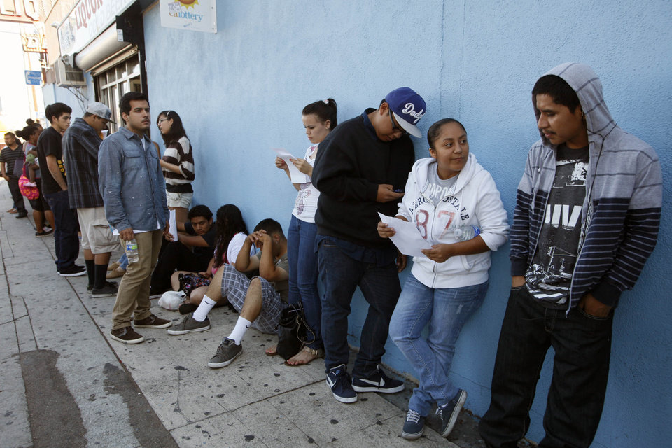 Photo -   A line of legal immigrants wait outside the Coalition for Humane Immigrant Rights in Los Angeles offices Wednesday, Aug. 15, 2012. Hundreds of thousands of young illegal immigrants scrambled to get papers in order, as the U.S. started accepting applications to allow them to avoid deportation and get a work permit, but not a path to citizenship. President Barack Obama announced the program in June after pressure from Hispanic voters and others who said he hasn't fulfilled a campaign promise to overhaul tangled U.S. immigration laws. (AP Photo/Nick Ut)