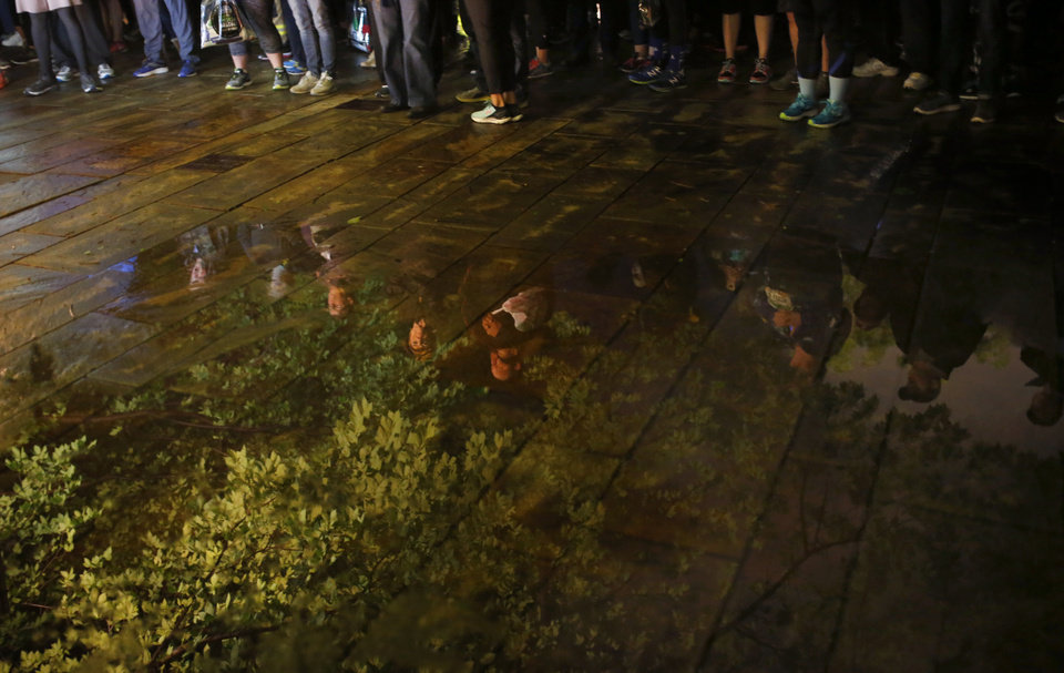Photo - Reflections of runners and the Survivor Tree are reflected in a puddle during the Sunrise Service before the 2017 Oklahoma City Memorial Marathon Sunday, April 30, 2017.  Photo by Sarah Phipps, The Oklahoman