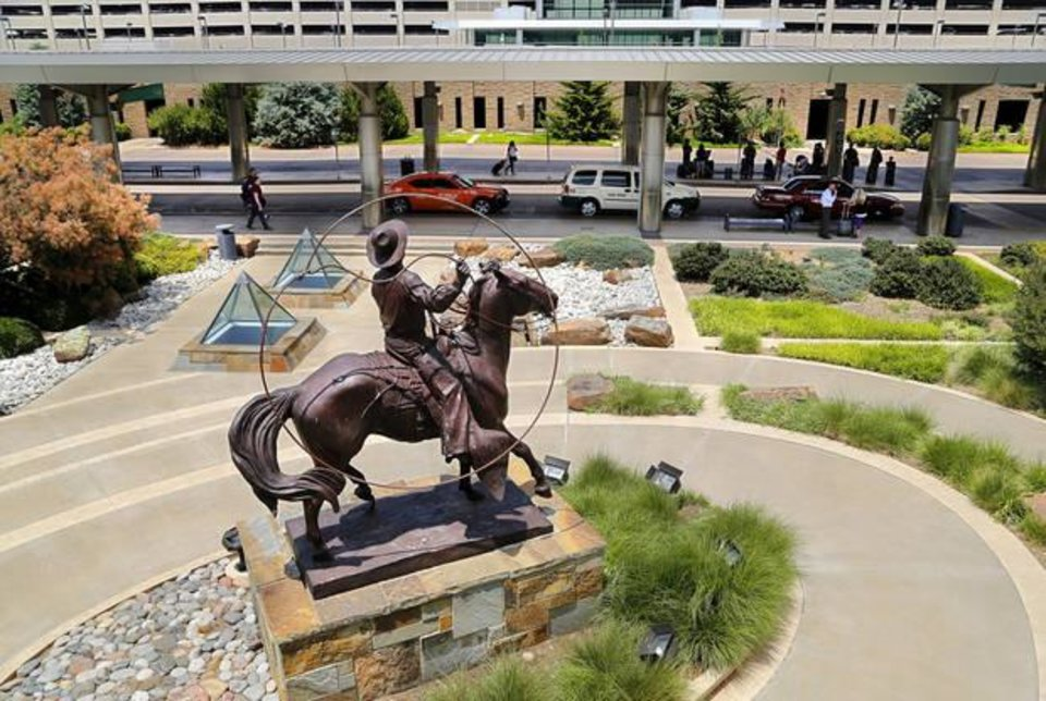 Photo - Travelers crossing from the new premium parking in Garage A at Will Rogers World Airport can pass the statue of Oklahoma favorite son and humorist Will Rogers astride his horse. [Photo by Jim Beckel/The Oklahoman]