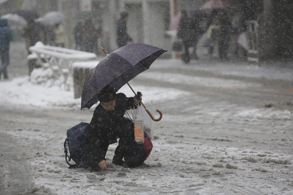 Photo - A student picks up a small change from the street in snowstorm in Yokohama, Japan, Saturday, Feb. 8, 2014. The Japan Meteorological Agency issued the first heavy snowfall warning for central Tokyo in 13 years.  Some 20-centimeter (7.9-inch) of snowfall is expected by Sunday morning in the metropolitan areas. (AP Photo/Eugene Hoshiko)