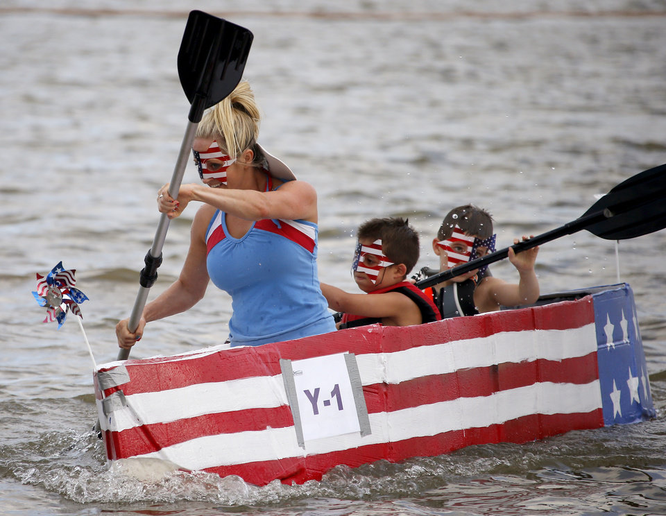 Photo -  Leah Sparks races Flag Boat with her children, Gavin, 6, center, and Kye, 9, during the family's fourth Cardboard Boat Regatta. PHOTO BY BRYAN TERRY, THE OKLAHOMAN   Bryan Terry -  THE OKLAHOMAN