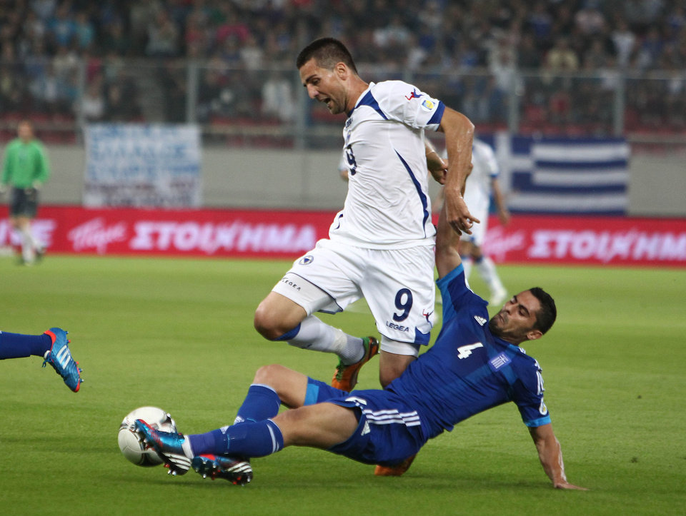 Greece's Nikos Spyropoulos, right, tries to stop Bosnia-Herzegovina's Vedad Ibisevic during their World Cup Group G qualifying soccer match at the Karaiskaki stadium in Piraeus port, near Athens, Thursday, Oct. 11, 2012. (AP Photo/Thanassis Stavrakis)