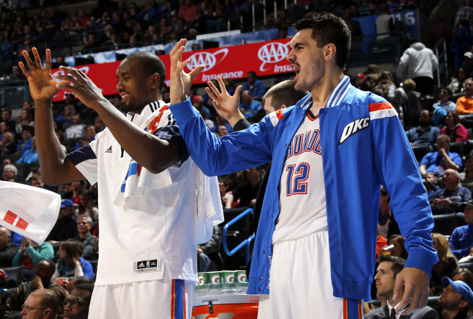 Photo - Oklahoma City's Steven Adams (12) and Serge Ibaka (9) celebrate from the bench during the NBA basketball game between the Oklahoma City Thunder and the Charlotte Hornets at the Chesapeake Energy Arena in Oklahoma City, Friday, Dec. 26, 2014. Photo by Sarah Phipps, The Oklahoman