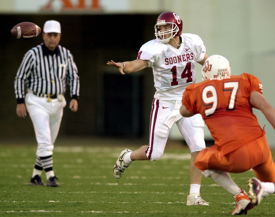 Photo - OU quarterback Josh Heupel pitches the ball in front of OSU's Zac Warner during the Bedlam college football game at Lewis Field in Stillwater, Okla., Saturday, Nov. 25, 2000. Staff Photo by Nate Billings.