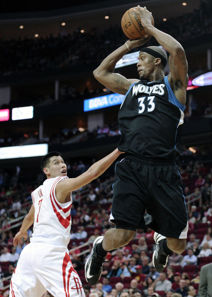 Photo - Minnesota Timberwolves' Dante Cunningham (33) looks to pass the ball over Houston Rockets' Jeremy Lin (7) in the first half of an NBA basketball game Friday, March 15, 2013, in Houston. (AP Photo/Pat Sullivan)