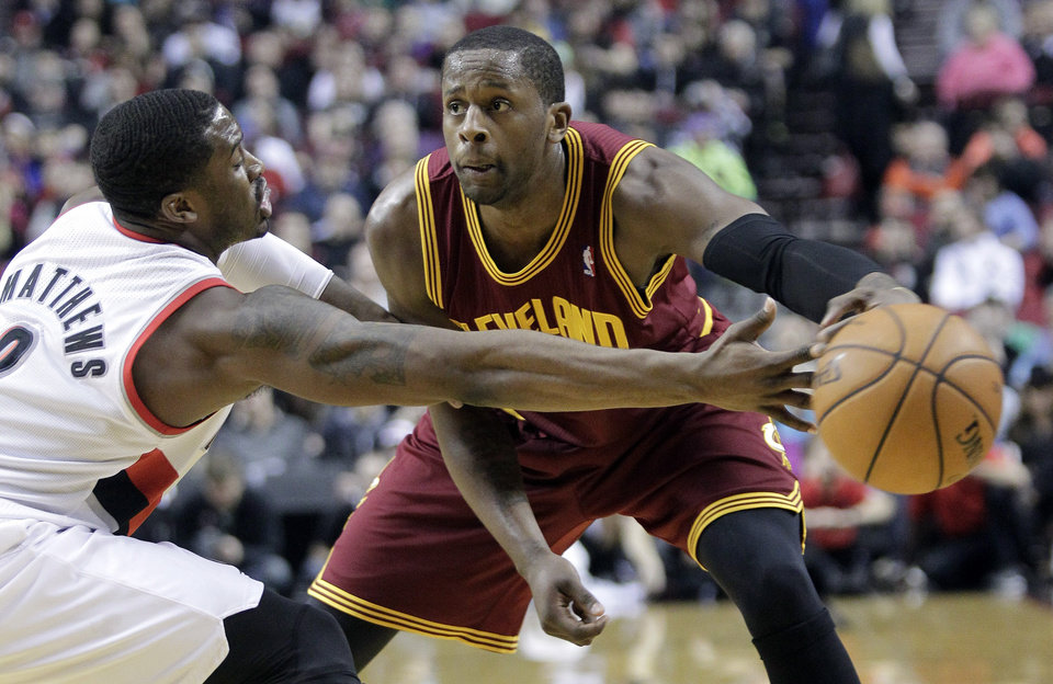 Photo - Cleveland Cavaliers guard C.J. Miles, right, passes inside against Portland Trails Blazers guard Wesley Matthews during the first half of an NBA basketball game in Portland, Ore., Wednesday, Jan. 15, 2014. (AP Photo/Don Ryan)