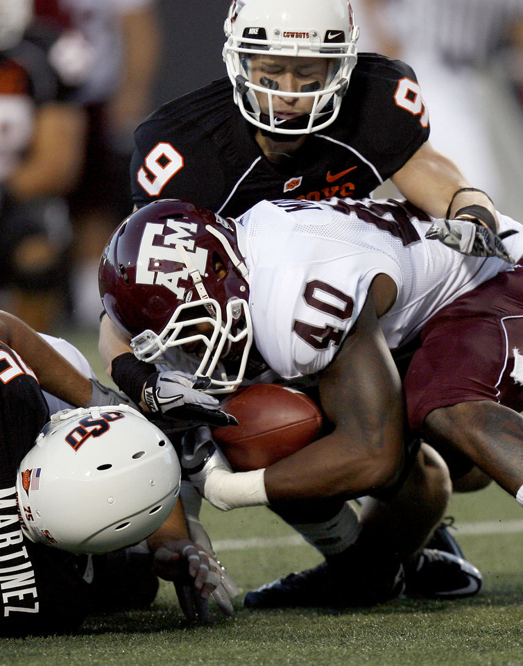 Photo - A&M's Von Miller recovers OSU's Brandon Weeden fumble as OSU's Bo Bowling (9) and Nick Martinez defend during the college football game between Texas A&M University (TAMU) and Oklahoma State University (OSU) at Boone Pickens Stadium in Stillwater, Okla., Thursday, Sept. 30, 2010. Photo by Sarah Phipps, The Oklahoman